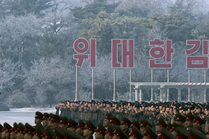 North Koreans clap beneath part of a slogan that calls on people to carry out the revolutionary ideology of late North Korean leaders Kim Il Sung and Kim Jong Il at the Kumsusan Palace of the Sun in Pyongyang, North Korea, Monday, Dec. 17, 2012. North Korean officials reopened the mausoleum on the first anniversary of the death of their former leader Kim Jong Il. (AP Photo/Ng Han Guan)