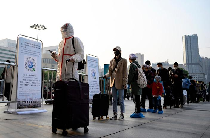 People arrive at Hankou Railway Station in Wuhan to take one of the first trains leaving the city in China's central Hubei province early on April 8, 2020.