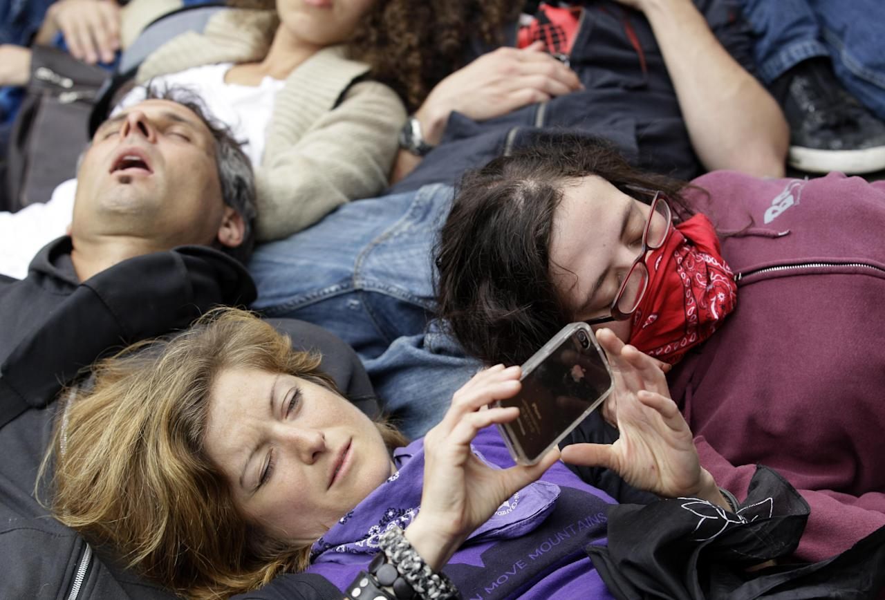 A protester uses her phone during a die-in at Boeing corporate offices as a part of the NATO summit Monday, May 21, 2012 in Chicago. (AP Photo/Nam Y. Huh)