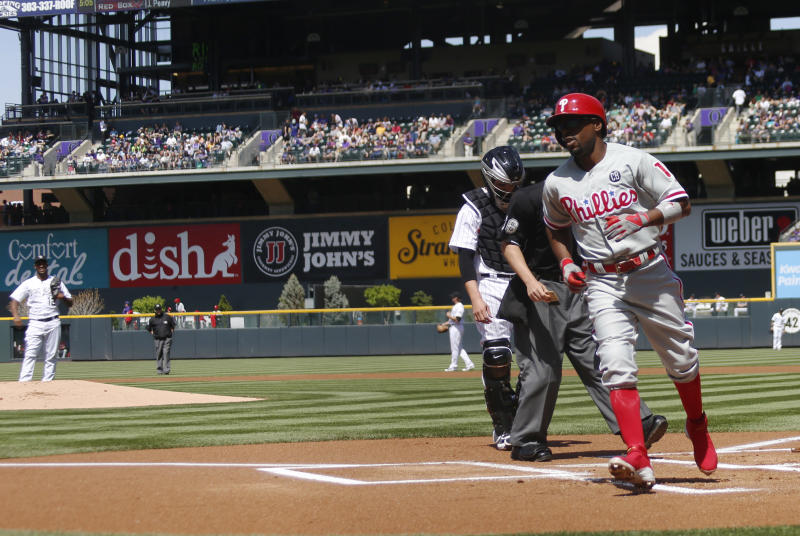 Philadelphia Phillies' JImmy Rollins, front, heads to dugout after crossing home plate following his solo home run off Colorado Rockies starting pitcher Juan Nicasio, rear left, in the first inning of a baseball game in Denver on Sunday, April 20, 2014. (AP Photo/David Zalubowski)