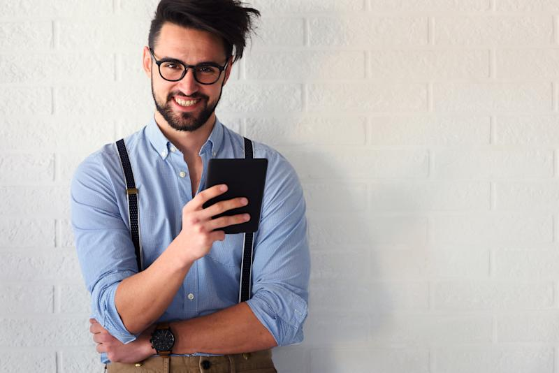 Portrait of handsome bearded hipster guy with glasses on standing indoors by the white brick wall. Using book reader.