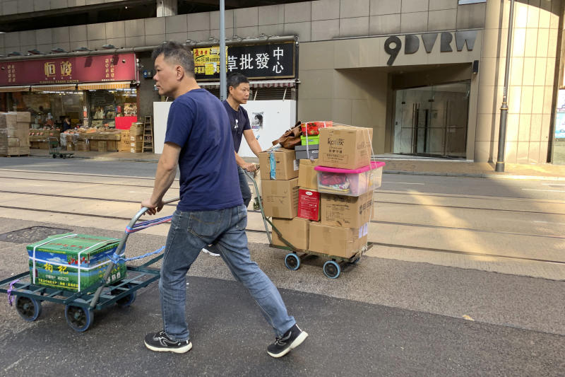 """Workers walk past a building listed as the address of China Innovation Investment Limited in Hong Kong, Saturday, Nov. 23, 2019. Australia's Treasurer on Saturday labeled detailed accusations of China infiltrating and disrupting democratic systems in Australia, Hong Kong and Taiwan as """"very disturbing"""". A Chinese defector revealed he was part of the Hong Kong-based investment firm, which was a front for the Chinese government to conduct political and economic espionage in Hong Kong, including infiltrating universities and directing bashings and cyber attacks against dissidents. (AP Photo/Ng Han Guan)"""