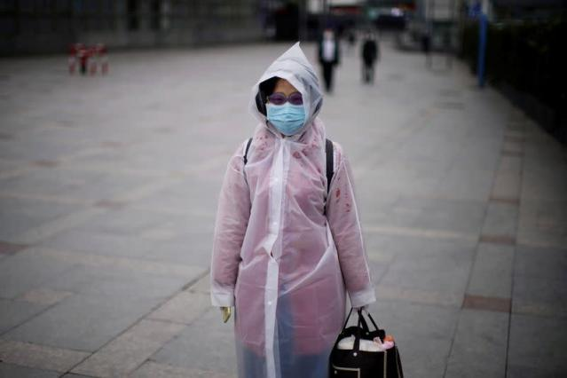 Passenger Chen, 28, wearing a mask and a swimming glasses walks outside the Shanghai railway station in Shanghai