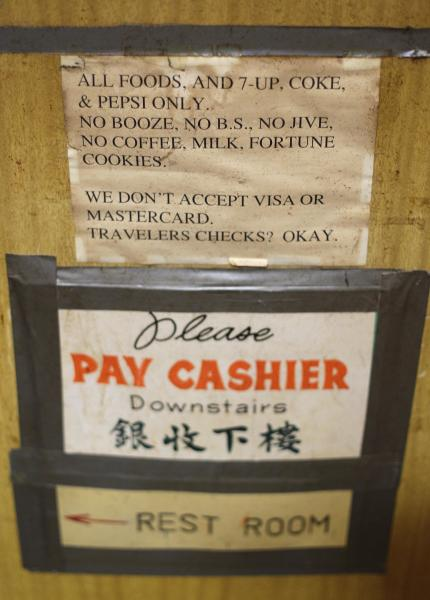 "Signs taped to the walls from long ago are shown inside the Sam Wo restaurant in Chinatown in San Francisco, Friday, April 20, 2012. The 100-year-old Chinese restaurant known for having ""the world's rudest waiter"" is shutting its doors and serving its last customers Friday. (AP Photo/Eric Risberg)"