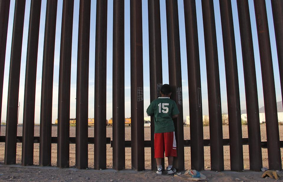 A Mexican child looks at a vehicle of the US border patrol through the US-Mexico fence in Ciudad Juarez, Chihuahua state, Mexico on 4 April, 2018. Human rights organisations have urged the US government to stop deporting Mexican children in rapid removals.  (AFP via Getty Images)