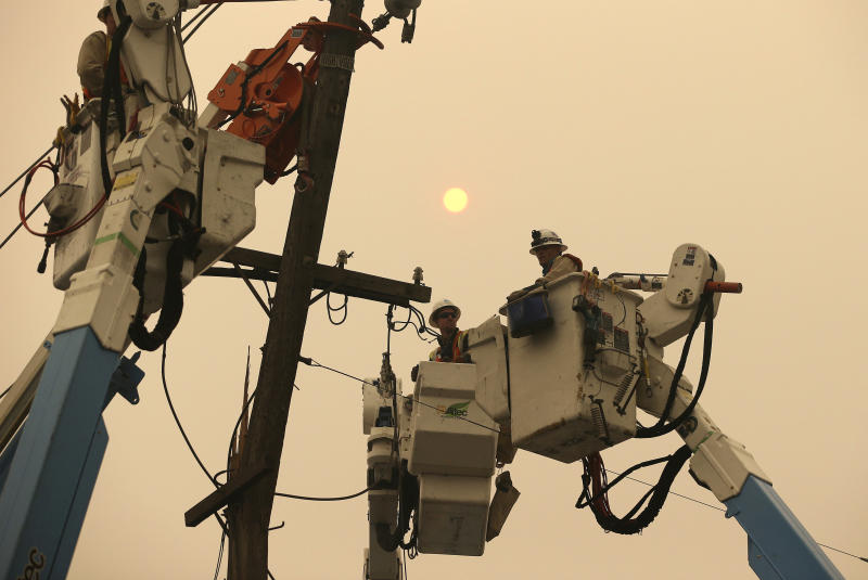 FILE - In this Nov. 9, 2018 file photo, Pacific Gas & Electric crews work to restore power lines in Paradise, Calif. Facing potentially colossal liabilities over deadly California wildfires, PG&E will file for bankruptcy protection. The announcement Monday, Jan. 14, 2019, follows the resignation of the power company's chief executive. (AP Photo/Rich Pedroncelli, File)