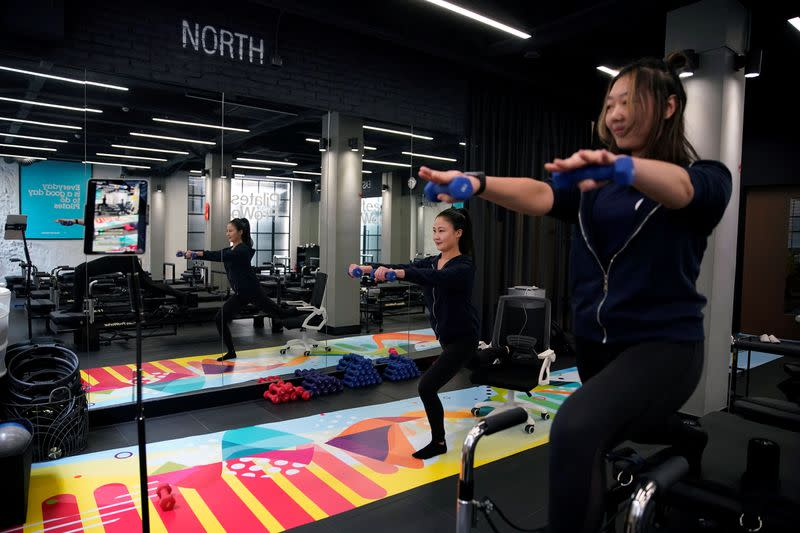 Fitness trainers Katie Xu and Heidi Liu lead exercise classes and stream them live at Pilates ProWorks studio in Shanghai
