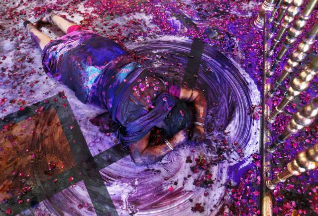 A Hindu woman prays while lying on the floor of a temple during Holi celebrations in the western Indian city of Ahmedabad March 17, 2014. Holi, also known as the Festival of Colours, heralds the beginning of spring and is celebrated all over India. REUTERS/Amit Dave (INDIA - Tags: SOCIETY RELIGION TPX IMAGES OF THE DAY)