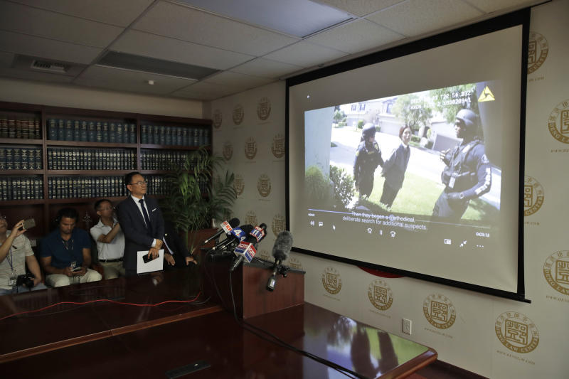 Dr. Henry Lee, left, a forensic scientist, watches a body cam video Wednesday, Aug. 28, 2019, in Rosemead, Calif. ,  of an arrest in the the city of Chino, which led to the death of a Chinese national. Lawyers are pursuing claims against a Southern California city for the fatal shooting of an unarmed man by a police officer who was part of team serving a search warrant on a suspected illegal marijuana operation. (AP Photo/Marcio Jose Sanchez)