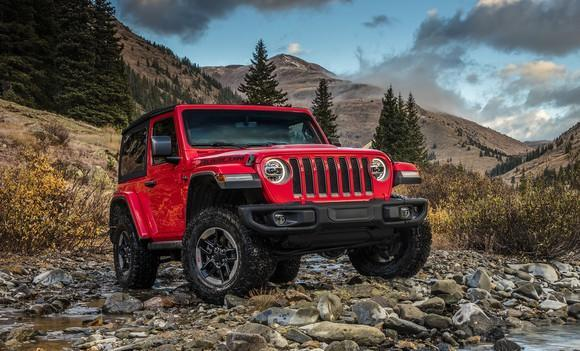 A red Jeep Wrangler Rubicon on a gravel road in the mountains.