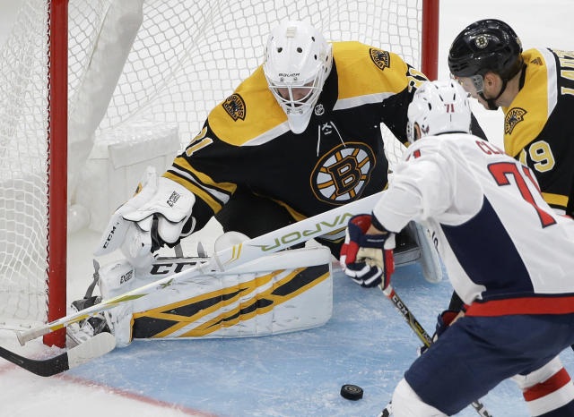 Boston Bruins' Zane McIntyre, left, deflects the puck as Washington Capitals' Kody Clark, second from right, tries to score and Bruins' Jeremy Lauzon, right, watches in the third period of an NHL preseason hockey game, Sunday, Sept. 16, 2018, in Boston. (AP Photo/Steven Senne)