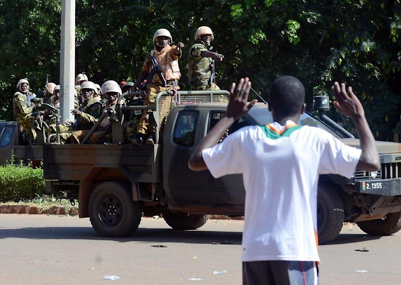 A man holds up his hands as Burkinese troops arrive at the national television headquarters after shots were fired around the premises in Ouagadougou on November 2, 2014 (AFP Photo/Issouf Sanogo)