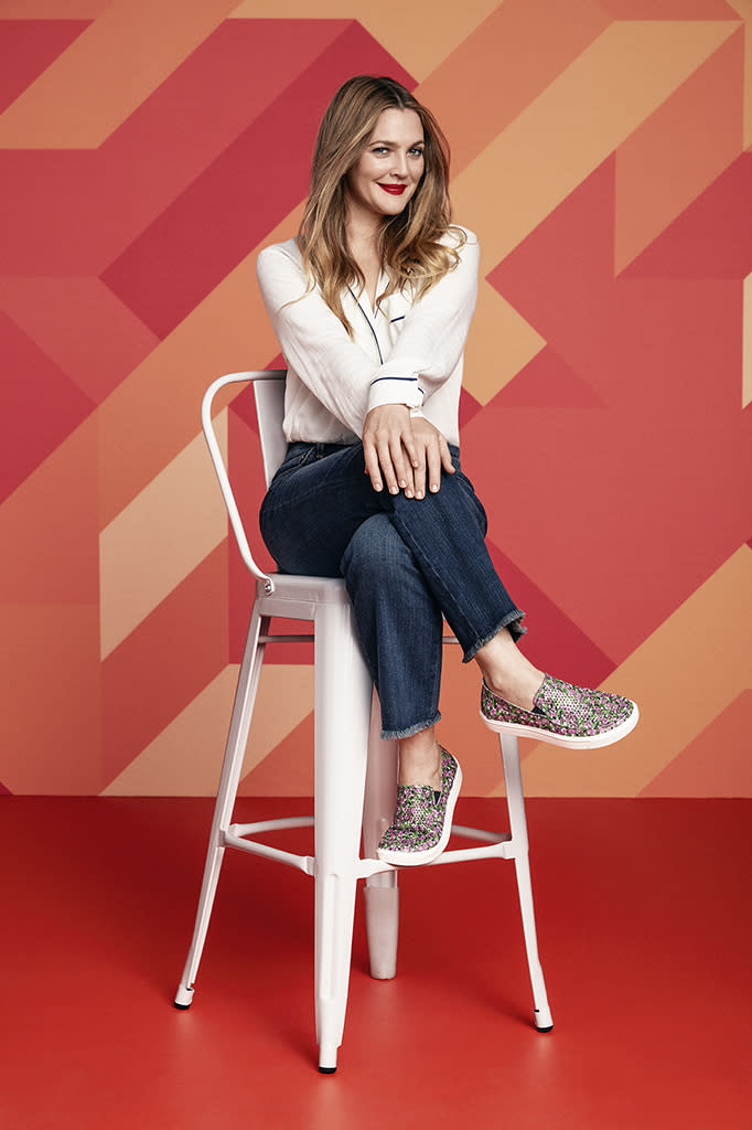 Drew Barrymore poses in a chair.