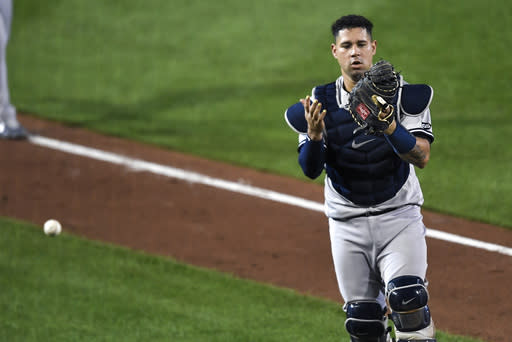 New York Yankees catcher Gary Snchez looks at his glove after dropping a foul hit by Toronto Blue Jays' Cavan Biggio during the fifth inning of a baseball game in Buffalo, N.Y., Tuesday, Sept. 8, 2020. (AP Photo/Adrian Kraus)