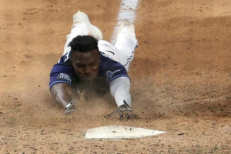 Uneasy slider: Randy Arozarena slides into home plate during the ninth inning to score the game winning run for Tampa Bay Rays in the World Series