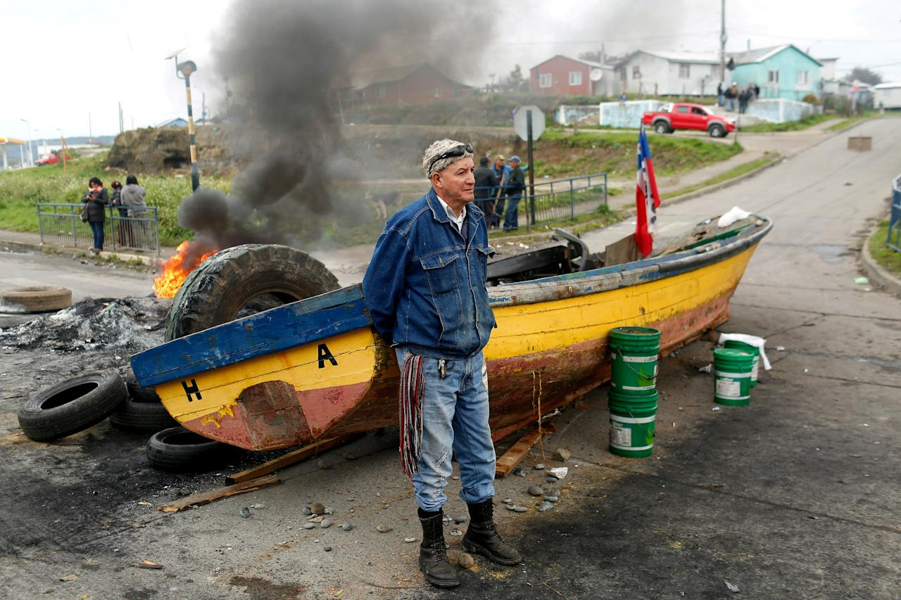 A fisherman stays next to a boat used to block a road during a protest calling on the government to help ease the economic effects of a harmful algal bloom that had affected their livelihoods at Ancud on Chiloe island in Chile, May 5, 2016. REUTERS/Pablo Sanhueza EDITORIAL USE ONLY. NO RESALES. NO ARCHIVE