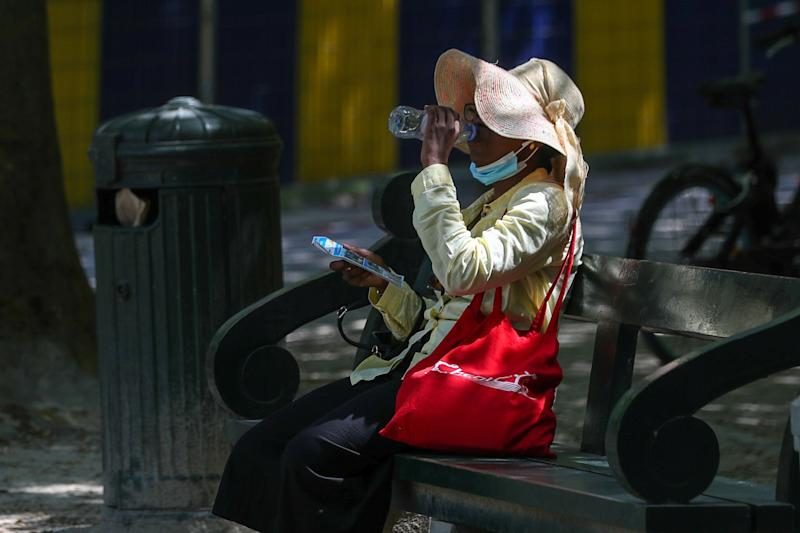 A woman drinks water as she sits on a bench during a heatwave, in Brussels, Belgium. (Photo: REUTERS/Yves Herman)