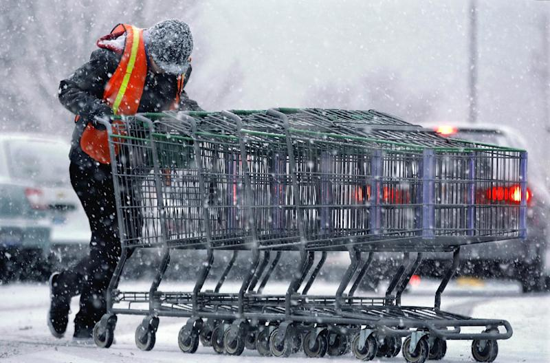 A shopping center employee struggles against strong winds and falling snow as a fast moving winter storm moves into the Midwest Friday, Dec. 13, 2013, in Springfield, Ill. A winter weather advisory extends from Missouri to western New York, according to the National Weather Service. Boston and most of southern New England may see 6 to 12 inches of snow while areas just north and east of the New York may get as much as 10 inches. (AP Photo/Seth Perlman)