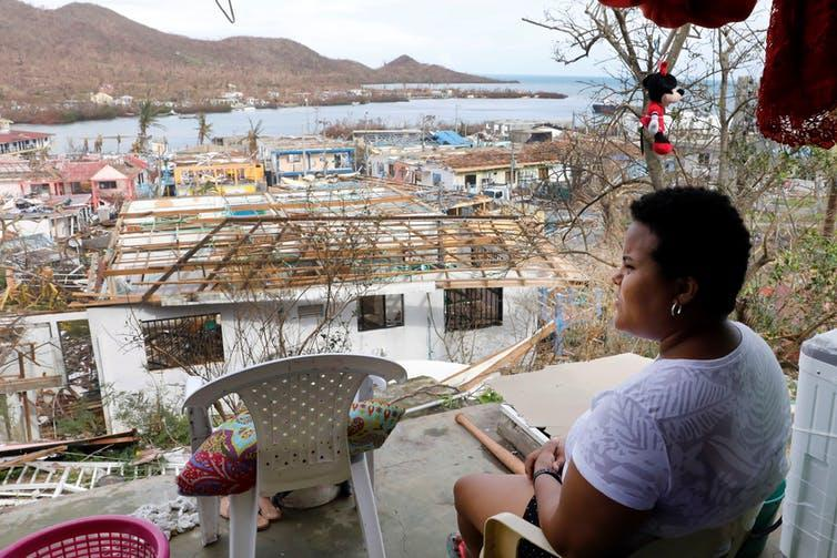 Woman looks away from camera at damaged buildings by the sea.