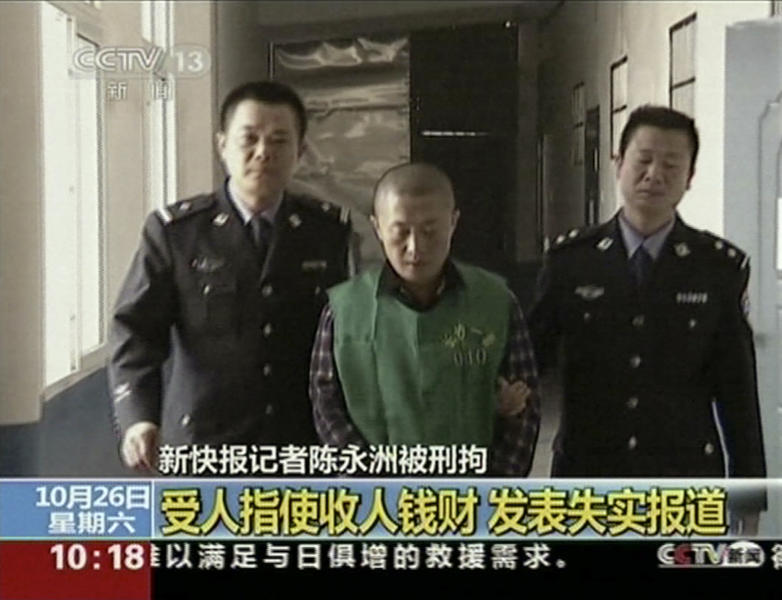 In this image taken from an Oct. 26, 2013 video footage run by China's CCTV via APTN, Chinese journalist Chen Yongzhou, center, is escorted by Chinese police officers during a broadcast that showed him confessing to taking money to smear a heavy machinery company in Changsha in south central China's Hunan province. The broadcast was the latest of several high-profile, televised confessions, a new tactic by Chinese authorities attempting to scrub information they deem harmful, illegal or false from the public domain, especially from the Internet. (AP Photo/CCTV via APTN) CHINA OUT, NO SALES, NO ARCHIVES, EDITORIAL USE ONLY