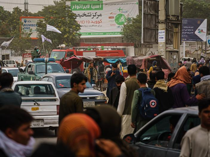 Afghans run away from Taliban fighters on airport road in Kabul, Afghanistan