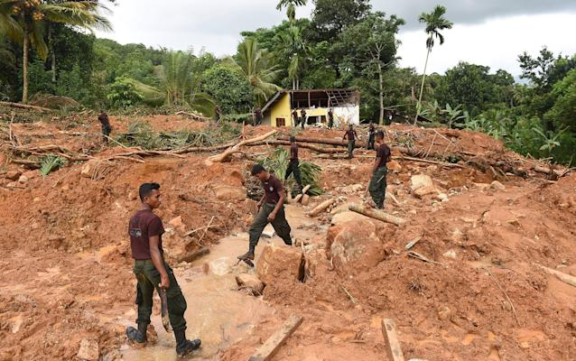 <p>Sri Lankan soldiers carry out recovery work at the site of a mudslide in the Kiribathgala village in Ratnapura district on May 31, 2017. Sri Lanka pledged May 31 to tighten construction laws as the toll from heavy rains rose, saying many landslide victims would have survived had their homes not been built on slopes. The government will also prosecute anyone violating existing rules by building on landslide-prone slopes, said Disaster Management Minister Anura Yapa. (Ishara S. Kodikara/AFP/Getty Images) </p>