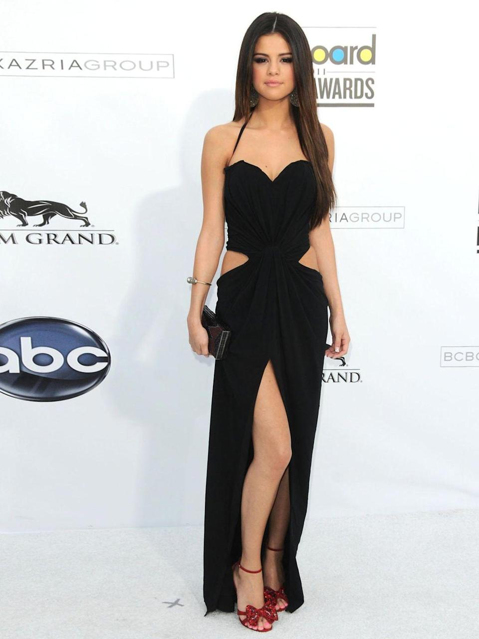 <p>Selena Gomez is at the Billboard Music Awards wearing a black Dolce & Gabbana cut out dress, May 2011.</p>