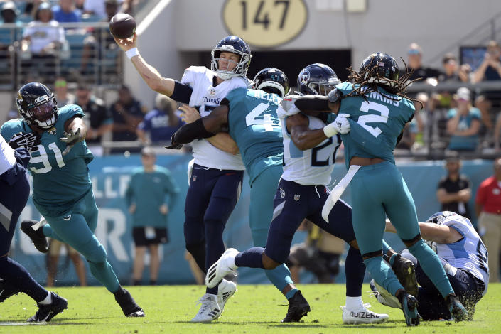 Tennessee Titans quarterback Ryan Tannehill, center, is hit by Jacksonville Jaguars outside linebacker Josh Allen (41) as he releases the ball during the first half of an NFL football game, Sunday, Oct. 10, 2021, in Jacksonville, Fla. (AP Photo/Phelan M. Ebenhack)