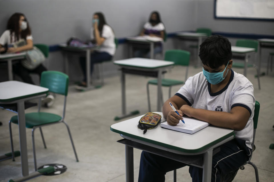 RIO DE JANEIRO, BRAZIL - NOVEMBER 24: A student wearing a face mask writes on his notebook during a class at the Carioca Coelho Municipal School of Application, in the Ricardo de Albuquerque neighborhood on November 24, 2020 in Rio de Janeiro, Brazil. Schools in Rio de Janeiro continue with the gradual reopening that began on November 17, after eight months due to the coronavirus pandemic. Only some students are resuming face-to-face activities, following strict protocols and with a limit of students per shift. (Photo by Bruna Prado/Getty Images)