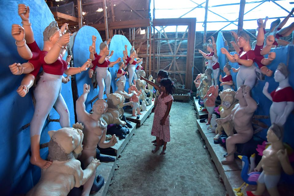 GUWAHATI, INDIA - OCTOBER 13, 2020: Childrens look incomplete idol of the Goddess Durga ahead of the upcoming 'Durga Puja' festival in Guwahati,india - PHOTOGRAPH BY Anuwar Ali Hazarika / Barcroft Studios / Future Publishing (Photo credit should read Anuwar Ali Hazarika/Barcroft Media via Getty Images)