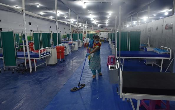 Cleaning staff at work at a temporary hospital with facilities for treatment of Covid-19 patients, at Patliputra Sports Complex in Patna, India.