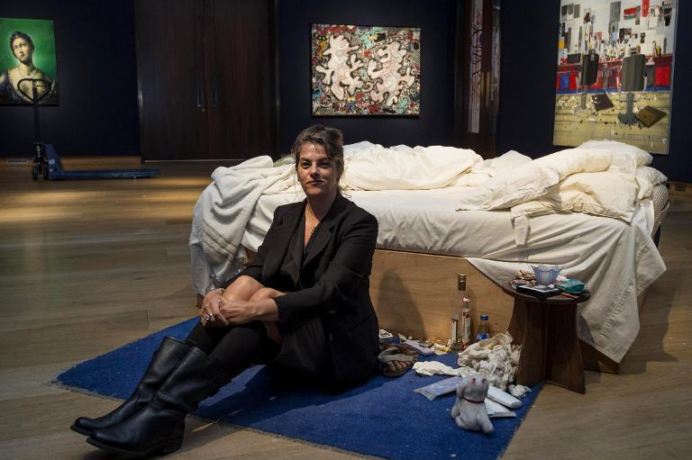 "British artist Tracey Emin sits on her iconic art installation, ""My Bed"", during a press preview at Christie's auction house in London on June 27, 2014 (AFP Photo/Niklas Halle'n)"