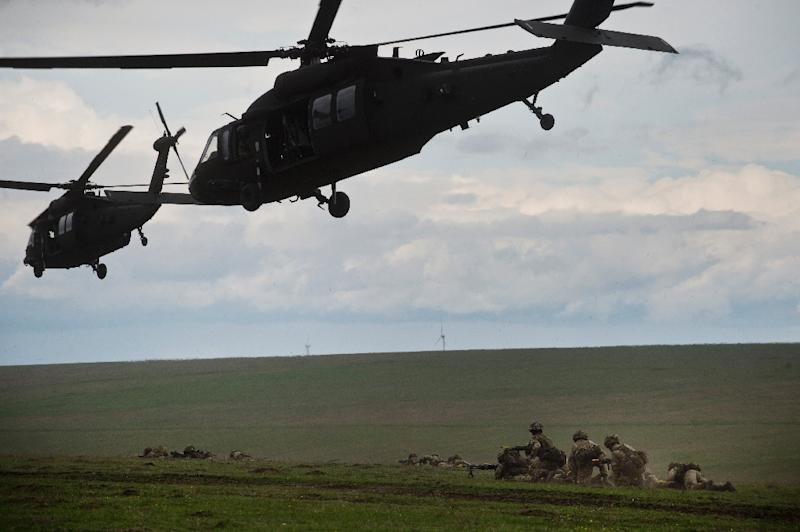 British servicemen under US Army choppers during NATO military exercise on April 21, 2015 in Smardan, Romania (AFP Photo/Daniel Mihailescu)