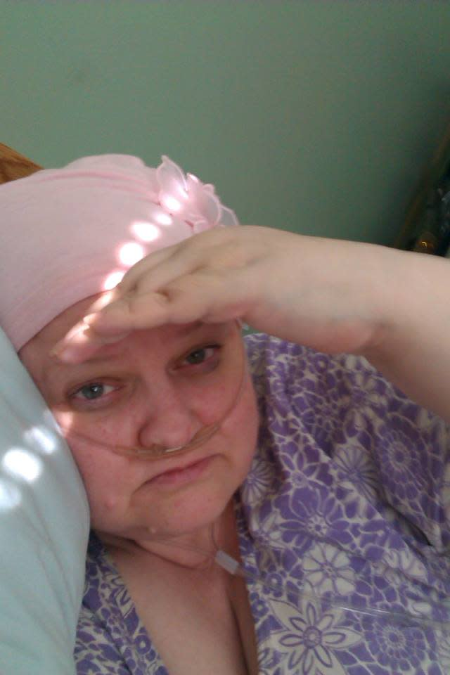 woman lying in bed with an oxygen tube in her nose and a pink scarf over her head