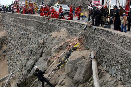 Rescue workers carry victims after a bus crashed with a truck and careened off a cliff along a sharply curving highway north of Lima, Peru, January 3, 2018. REUTERS/Guadalupe Pardo