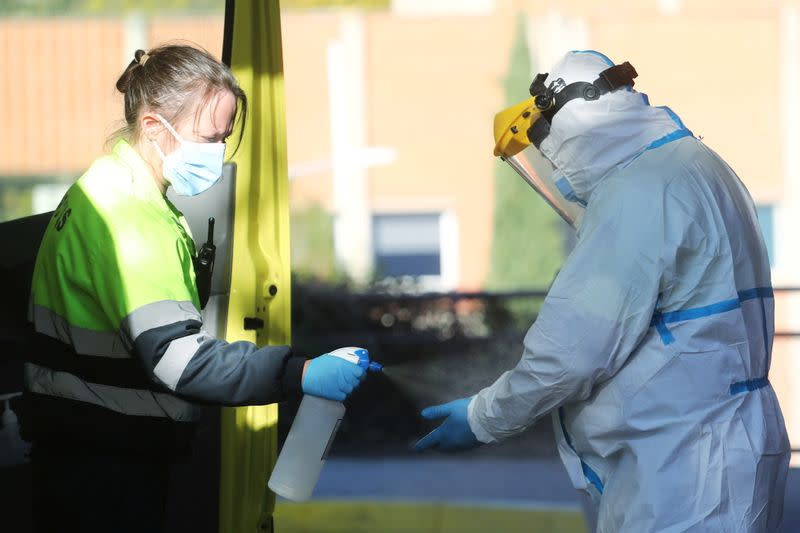 FILE PHOTO: An ambulance worker wearing a full personal protective equipment (PPE) is disinfected by a collage in Leganes