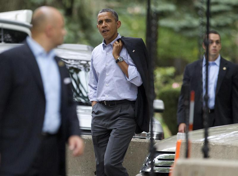 President Barack Obama, center, walks through his Hyde Park neighborhood to a campaign event, Sunday, Aug. 12, 2012, in Chicago. (AP Photo/Carolyn Kaster)