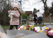 A young girl lays a floral tribute to Captain Tom Moore in Marston Moretaine, England, Wednesday, Feb. 3, 2021. Captain Tom Moore, the 100-year-old World War II veteran who captivated the British public in the early days of the coronavirus pandemic with his fundraising efforts for medical care workers, died Tuesday. (AP Photo/Alastair Grant)