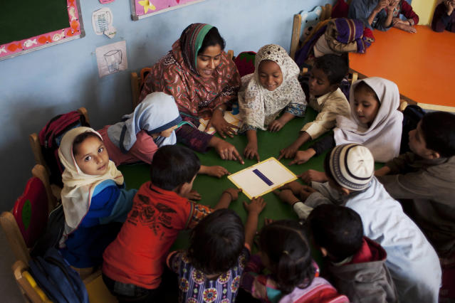 <p>Pakistani students gather around Humaira Bachal, the founder of a charity school as she teaches them in a classroom in Karachi, Pakistan, Feb. 24, 2014. (AP Photo/Shakil Adil) </p>