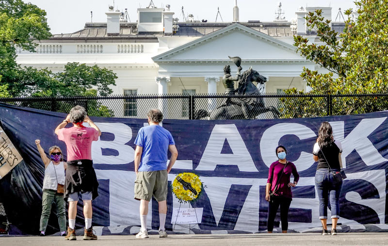 People pose in front of the fence at the north side of Lafayette Square in Washington, D.C. on June 9, 2020. (Bonnie Jo Mount/The Washington Post via Getty Images)