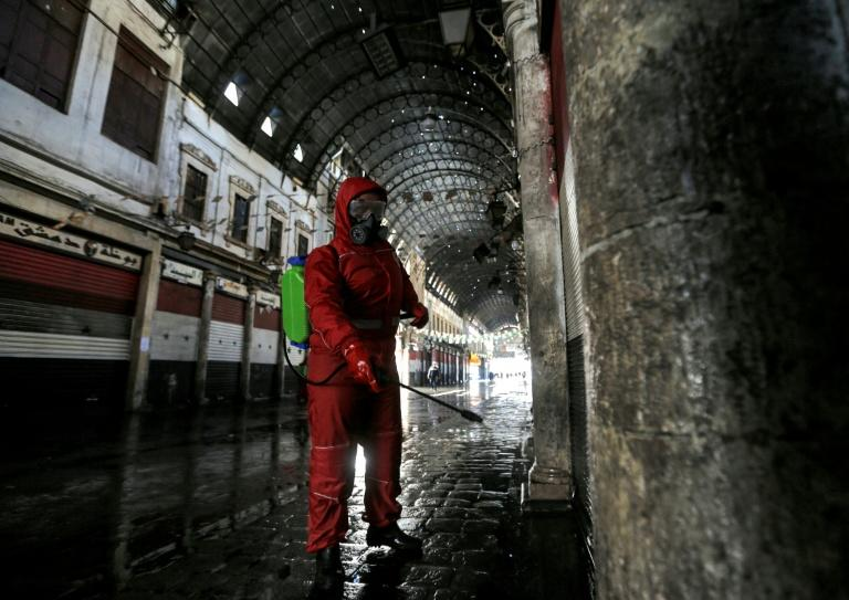 A Red Crescent member sprays disinfectant along an alley of the historic Hamidiya souk (market) in the old city of Syria's capital Damascus as part of efforts against the coronavirus pandemic