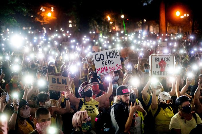 Hundreds of Black Lives Matter protesters hold their lighted phones aloft in Portland, Ore., on July 20, 2020.