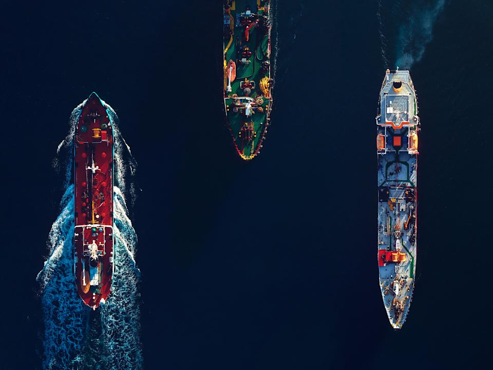 Marine traffic of a busy harbour. Nautical vessels cruising close to each other at different directions in the port.