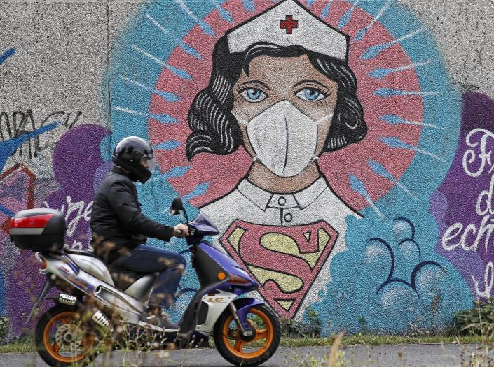A man on a scooter passes a graffiti by street artist 'Uzey', depicting a nurse as superhero in the coronavirus pandemic on a wall in Hamm, Germany, Monday, Sept. 28, 2020. The city of Hamm is the number one coronavirus hotspot at the moment in Germany, with a sudden increase of Covid-19 infections. Most of them are related to a wedding with more than 300 guests. (AP Photo/Martin Meissner)