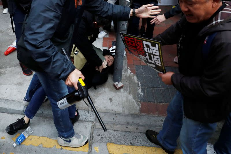 A woman is detained by plain-cloth police officers during an anti-government demonstration on New Year's Day, to call for better governance and democratic reforms in Hong Kong