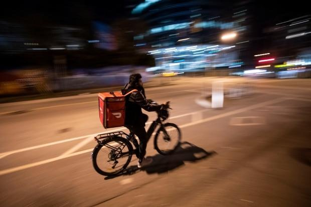 A food delivery service employee rides his bicycle in downtown Vancouver. Restaurant owners want tighter regulation on multinational third-party delivery apps like Doordash, SkipTheDishes and UberEats. (Ben Nelms/CBC - image credit)