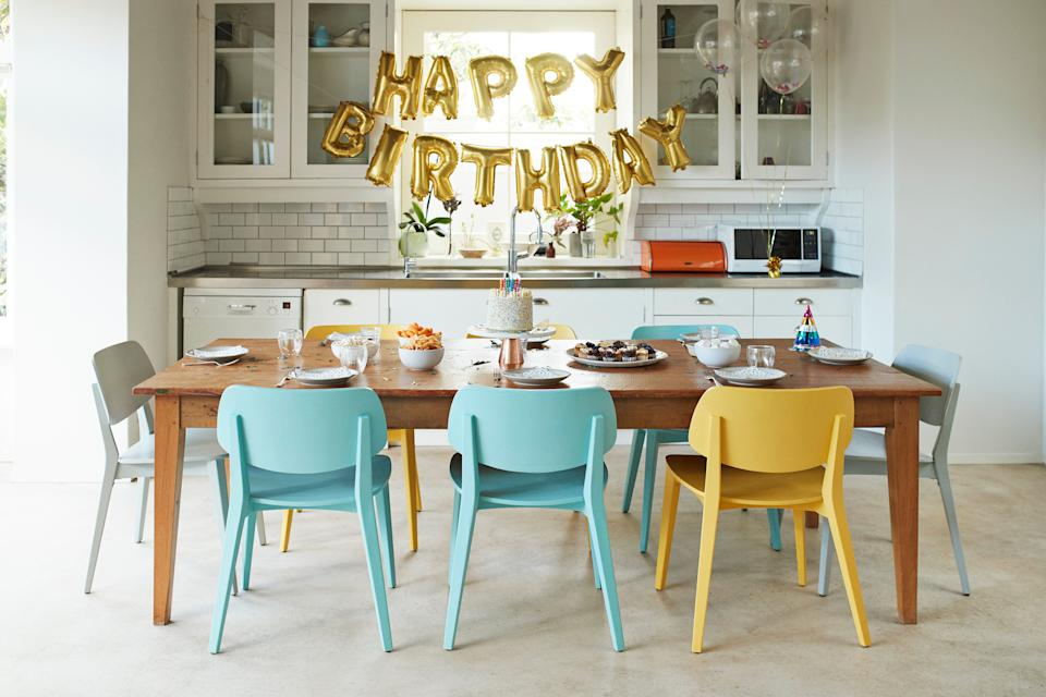 Chairs arranged around dining table in kitchen during birthday party at home (Photo: Klaus Vedfelt via Getty Images)