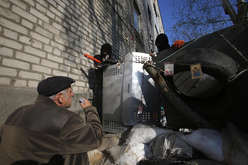 An elderly man talks with pro-Russian protesters guarding a barricade in Slovyansk, eastern Ukraine, Wednesday, April 16, 2014. The city of Slovyansk has come under the increasing control of the pro-Russian gunmen who seized it last weekend. (AP Photo/Sergei Grits)