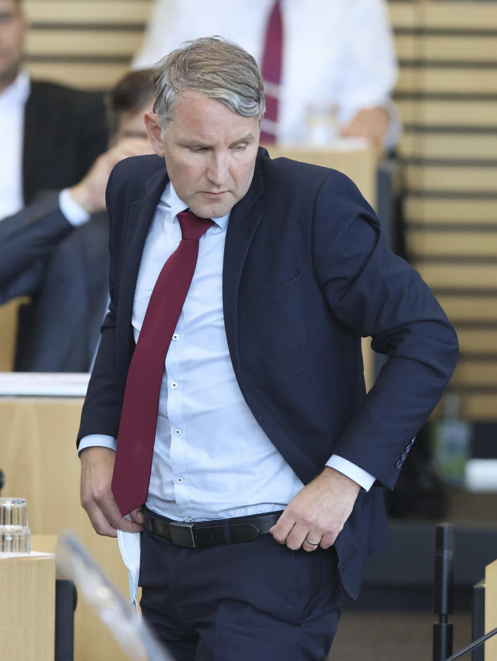 Bjoern Hoecke, parliamentary group leader of the AfD in the Thuringian state parliament, stands on his seat in the plenary hall during the vote in Erfurt, Germany, Friday, July 23, 2021. The far-right Alternative for Germany party failed in an attempt Friday to unseat the left-wing governor of an eastern German state, a long-shot bid that opponents denounced as political theater. (Bodo Schackow/dpa via AP)