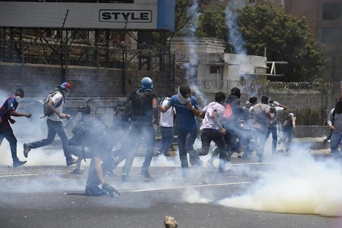 Demonstrators protesting against President Nicolas Maduro's government, for the fifth time in the past week, clash with riot police in Caracas, on April 10, 2017 (AFP Photo/Juan Barreto)
